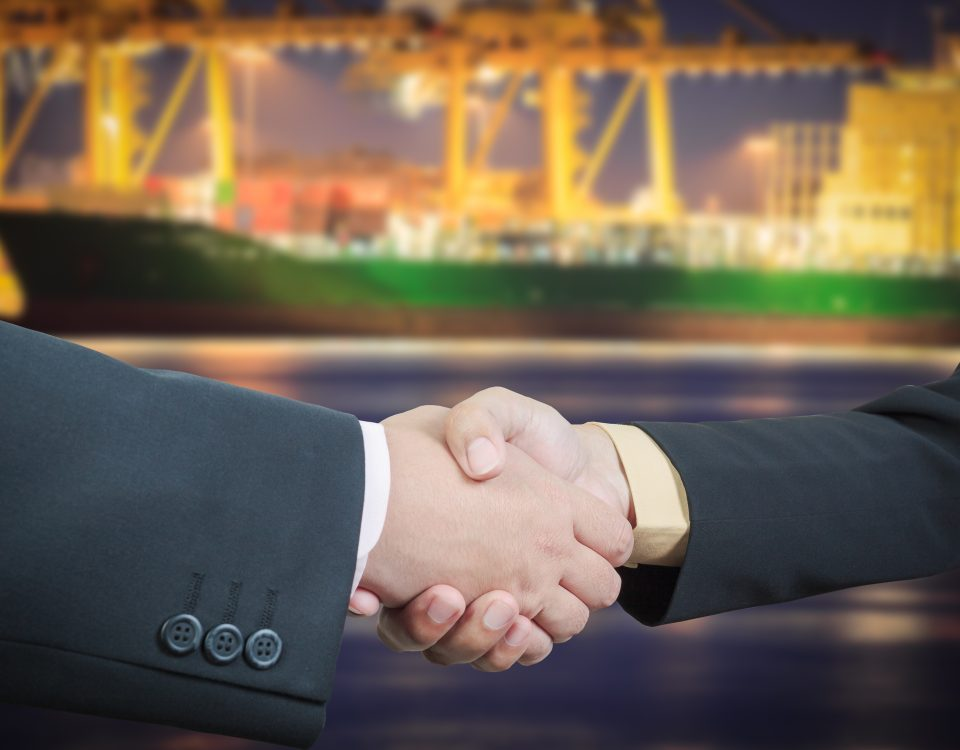 Businessman handshake with ship transportation logistic background