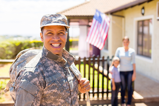 soldier returning home with family on background